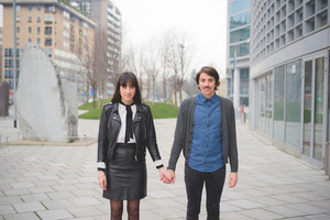 Knee figure of a couple of young caucasian man and woman posing in the streets of the city hand in hand- carefree, friendship, love, youth concept