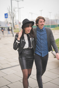 Knee figure of a couple of young caucasian man and woman walking trough the streets of the city hugging and smiling - carefreeness, friendship, love, youth concept