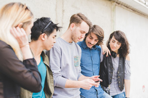 Knee figure of a group of young multiethnic friends leaning on a wall chatting to each other having fun using smartphone - social network,technology, communication, technology concept