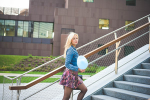 Knee figure of a young beautiful blonde caucasian girl climb staircase with a hearted balloon looking in camera wearing jeans shirt and floral skirt- youth, carefreeness, freshness concept