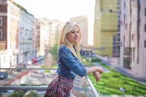 Knee figure of a young beautiful blonde caucasian girl posing leaning on a windowsill in the city wearing a jeans shirt and a floral skirt overlooking on her left - youth, freshness concept