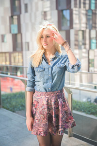 Knee figure of a young beautiful blonde caucasian girl posing outdoor in the city wearing a jeans shirt and a floral skirt overlooking right - freshness, carefreeness, youth concept