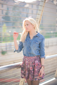 Knee figure of a young beautiful blonde girl posing outdoor in the city overlooking on her right wearing a jeans shirt and a floral skirt