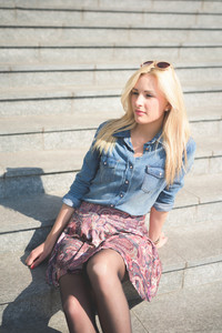 Knee figure of a young beautiful blonde girl posing seated on a staircase outdoor in the city overlooking on her right wearing a jeans shirt and a floral skirt - youth, carefreeness, freshness concept
