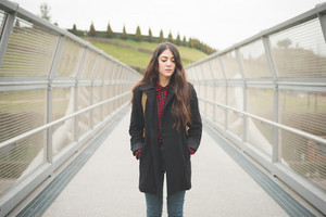 Knee figure of a young beautiful brunette long hair pensive and melancholic woman posing in the city in winter outdoor - concept of humas emotions - dressed with black coat and checked red shirt