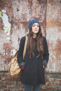 Knee figure of a young beautiful brunette  long hair pensive woman posing in the city in winter outdoor - concept of humans emotions