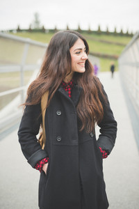 Knee figure of a young beautiful brunette long hair woman smiling walking on a bridge - concept of human emotions, optimism, trust in future - dressed with black coat and checked red shirt