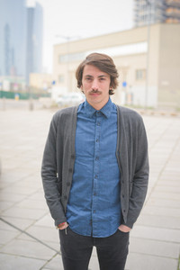 Knee figure of a young beautiful caucasian brown hair man with moustache posing through the streets of the city looking in camera - Freshness, serene, carefreeness concept