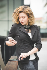 Knee figure of a young beautiful caucasian contemporary businesswoman leaning on a railing using smartphone and tablet looking down on the screen - technology, network, business, finance concepts
