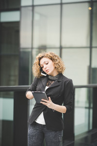 Knee figure of a young beautiful caucasian contemporary businesswoman talking smartphone while using a tablet looking down the screen- technology, network, business, finance concepts