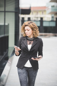 Knee figure of a young beautiful caucasian contemporary businesswoman walking through the city using smartphone and tablet looking the screen- technology, network, business, finance concepts