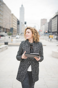 Knee figure of a young beautiful caucasian contemporary businesswoman walking through the streets of the city using a tablet overlooking - technology, network, business, finance concepts