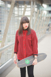 Knee figure of a young beautiful caucasian woman walking through the streets of the city with a skateboard posing and looking in camera - youth, freshness, carefree concept