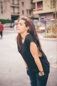 Knee figure of a young beautiful reddish brown hair caucasian girl with hands in pocket posing in the street - carefreeness, freshness, youth concept - dressed with blue jeans and black shirt