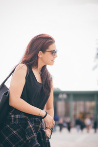 Knee figure of a young beautiful reddish brown hair caucasian girl with sunglasses smiling overlooking right - carefreeness, freshness, youth concept - dress with black shirt