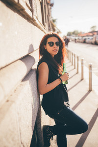 Knee figure of a young beautiful reddish brown hair caucasian woman leaning against a wall drinking a beer - carefreeness, freshness, youth concept - dressed with blue jeans and black shirt
