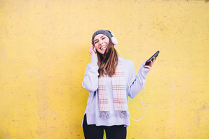 Knee figure of a young beautiful woman leaning on a yellow wall listening music with headphones and smart phone hand hold, laughing and dancing - happiness, music, dance concept