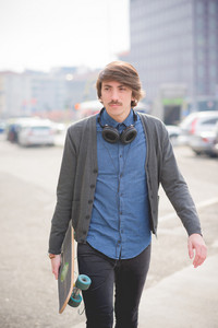 Knee figure of a young handsome caucasian man with moustache walking through the streets with a skate listening to music by headphones - sportive, music, relaxing concept