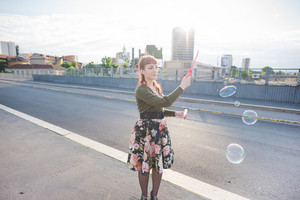 Knee figure of a young handsome caucasian redhead woman playing with bubble soap in the city overlooking right - childhood, youth concept - wearing floral skirt and green shirt