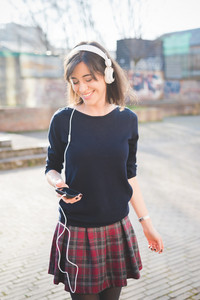 Knee figure of a young pretty brown hair caucasian girl listening music with headphones, holding a smartphone in her hand, looking downward, dancing and smiling - music, relaxing, happiness concept