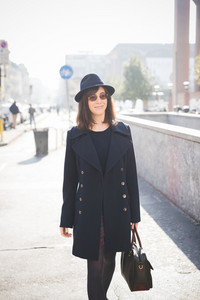 Knee figure of a young pretty caucasian brown hair woman posing in the street of the city with a pair of sunglasses, a black coat and a hat, overlooking left, smiling - amusement, relaxing concept