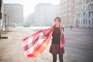 knee figure of a young pretty caucasian brown hair woman, seen from behind, posing in the street of the city, playing and dancing with her colorful scarf - carefreeness, youth, happiness concept