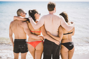 Knee figure of group of young multiethnic friends women and men at the beach in summertime hugging back watching sunset - teamwork, friendship concept
