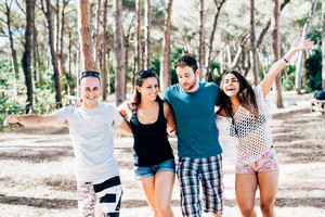 Knee figure of group of young multiethnic friends women and men walking in a pinewood hugging, having sun laughing - happiness, having fun, friendship concept