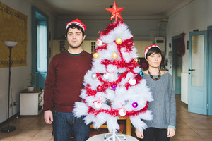 Knee figure of handsome caucasian man and woman couple posing near the christmas tree serious -  christmas, celebration concept