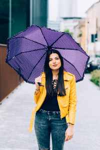 Knee figure of long straight hair woman walking outdoor in the city holding an umbrella in a rainy day - happiness, carefree, serene concept