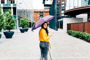 Knee figure of long straight hair woman walking outdoor in the city holding an umbrella in a rainy day, using smart phone - technology, social network, communication concept