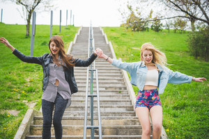 Knee figure of two beautiful blonde and brunette girl jumping down the stairs of a city park, hand in hand - friendship, emancipation, carefreeness concept