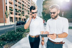 Knee figure of two handsome bearded business man outdoor in the city, one talking smart phone, the other using a tablet hand hold - business, start up, finance, technology concept