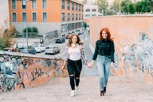 Knee figure of two handsome caucasian women friends walking hand in hand with headphones around her neck, laughing and having fun - happiness, friendship, music concept