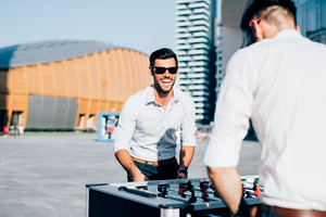 Knee figure of two modern bearded businessman playing table football during a break, focus on the blonde one - having fun, break, playing concept