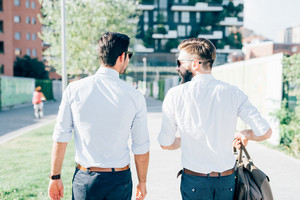 Knee figure of two young bearded blonde and black hair modern businessman, walking in the city backlight, view from back - working, successful concept