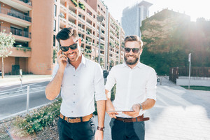 Knee figure of two young bearded blonde and black hair modern businessman, walking in the city, talking smartphone and using tablet - technology, business, work concept - shot in backlight