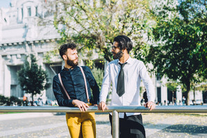 Knee figure of two young bearded contemporary businessman outdoor in the city discussing and planning together - inspiration, planning, project concept