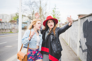 Knee figure of two young beautiful blonde and brunette girls having fun in the city taking selfie with smartphone - technology, vanity, social network concept