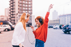 Knee figure of two young beautiful redhead and blonde woman listening music with headphones and smart phone hand hold, dancing outside in the city - happiness, freedom, having fun concept