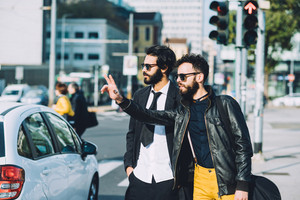 Knee figure of two young handsome caucasian bearded brown hair businessmen outdoor in the city, asking for a taxi - business, technology, communication concept