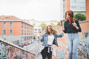 Knee figure of two young handsome caucasian blonde and redhead straight hair women dancing in the city listening music with headphones and smartphone, laughing - music, fun, freedom concept