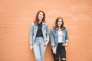 Knee figure of two young handsome caucasian blonde and redhead straight hair women posing leaning against a wall, smiling - having fun, friendship concept