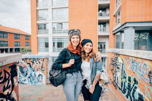 Knee figure of two young handsome caucasian blonde and redhead straight hair women walking hugging outdoor in the city, laughing, looking in camera - having fun, carefree, youth concept