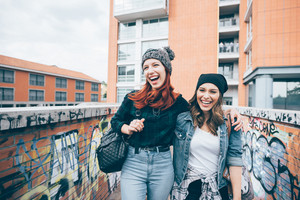Knee figure of two young handsome caucasian blonde and redhead straight hair women walking hugging outdoor in the city, laughing, looking over - having fun, carefree, youth concept
