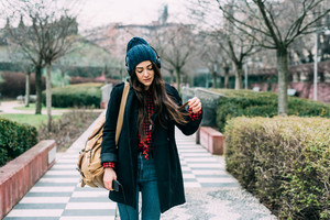 Knee figure of young beautifu caucasian long brown hair woman walking outdoor in the city listening music with headphones an smartphone hand hold - technology, music, relaxing concept