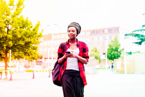 Knee figure of young beautiful black woman walking outdoor in the city using smart phone hand hold, looking over serene - technology, carefree, music concept