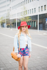 Knee figure of young beautiful blonde caucasian girl posing in the city suburbs dressed with a red hat, a pair of floral shorts and a jeans jacket, looking in camera - youth, fashion concept