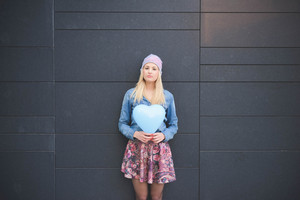 Knee figure of young beautiful blonde girl posing leaning on a wall with a hearted balloon outdoor in the city looking in camera wearing a jeans shirt, a hat, and a floral skirt