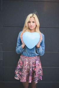 Knee figure of young beautiful blonde girl posing leaning on a wall with a hearted balloon outdoor in the city overlooking right wearing a jeans shirt, a hat, and a floral skirt
